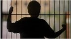Silhouette of child behind bars