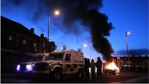 Police stand by their armoured vehicles as a car burns following violence between, loyalists, nationalists and the police in east Belfast