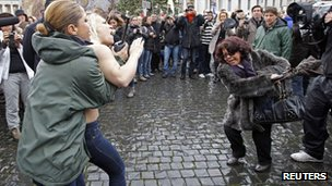 A Femen activist is restrained by a policewoman at the Vatican (13 Jan 2013)