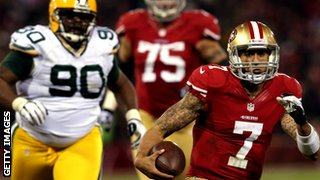 Colin Kaepernick of the San Francisco 49ers (right) powers through the Green Bay defence
