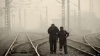 Two Chinese men walking along a railway line in Beijing, January 12, 2013