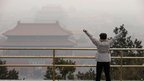 A visitor stretches her arms as she looks over the Forbidden City through severe haze in Beijing Sunday, Jan. 13, 2013
