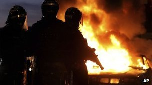 Riot police stand next to a burned out car after Loyalist protesters attacked police lines, in east Belfast
