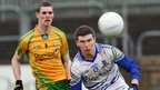 Caolan Ward of Donegal looks on as Monaghan player Keith McEneaney keeps his focus on the ball at Ballybofey