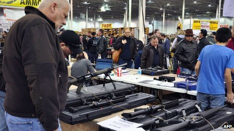 Gun show goers look at various assault-style weapons December 30, 2012 at the Nation&quot;s Gun Show in Chantilly, Virginia