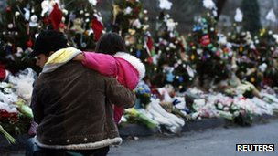 A woman holds a child next to a makeshift memorial for victims who died in the December 14 shootings at Sandy Hook Elementary School, in Newtown, Connecticut December 18,