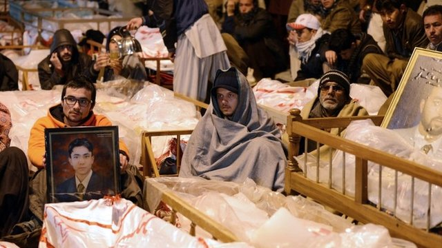 Protesting mourners sit by the shrouded bodies of their dead in Quetta, Pakistan, 12 January