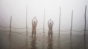 Devotees pray while taking a dip at the Sangham or confluence of the Yamuna and Ganges river at day break at the Kumbh Mela celebration in Allahabad on 13 January, 2013