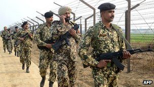 Indian Border Security Force soldiers patrol along the India-Pakistan border fence about 27 KM from Wagah on January 13, 2013
