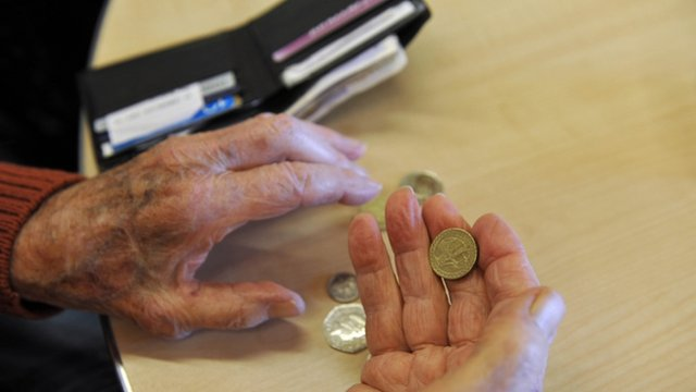 Elderly person holds money