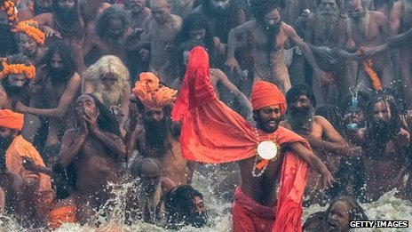 Naga sadhus run in to bathe in the waters of the holy Ganges river during the auspicious bathing day of Makar Sankranti of the Maha Kumbh Mela on 14 January 2013 