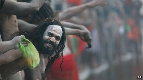 A Naked Hindu holy man or a Naga Sadhu watches others as they wait for a dip at Sangam