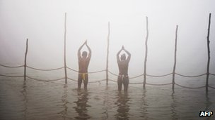 Devotees pray while taking a dip at the Sangham or confluence of the Yamuna and Ganges river at day break at the Kumbh Mela celebration in Allahabad on January 13, 2013.