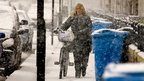 Cyclist walking through the snow