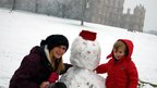 Woman and boy build a snowman at Wollaton Hall