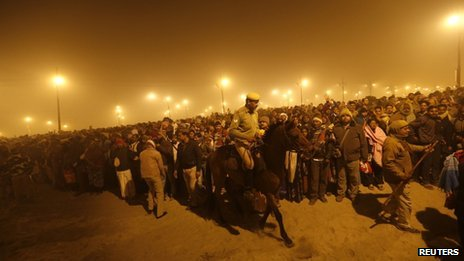 "A policeman mounted on his horse maintains order during the first ""Shahi Snan"" (grand bath) at the ongoing ""Kumbh Mela"