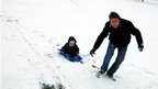 Man takes his son sledging at Wollaton Hall in Nottingham