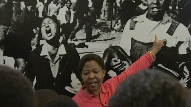 Antoinette Sithole shows a group of schoolchildren a picture of herself as a schoolgirl, screaming after her brother was shot and killed by the police in June 1976