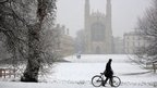 A man wheels a bicycle past Kings College in Cambridge