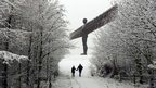 A couple walk through the snow towards the Angel of the North statue near Gateshead