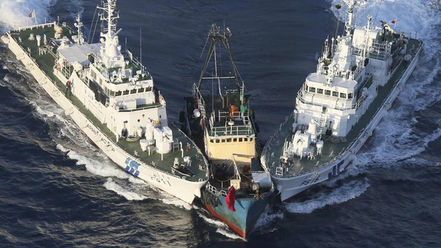 A fishing boat is surrounded by two Japanese Coast Guard patrol boats
