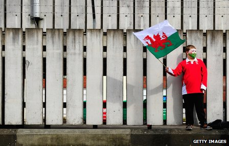 A fan waves his flag as Wales win the rugby Grand Slam after the Six Nations match between Wales and France at the Millennium stadium on 17 March 2012 in Cardiff, Wales