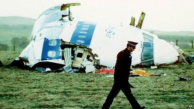 A police officer walks by the nose of Pan Am flight 103 in a field near the town of Lockerbie