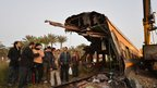 People inspecting the wreckage of a train in the Giza in Badrashin, about 40km south of Cairo, on 25 January 2013