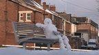 Snowman sitting on park bench reading newspaper