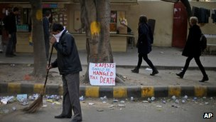 An Indian municipal worker sweeps a road as a placard, demanding death penalty for rapists, is placed on a sidewalk in New Delhi, India.