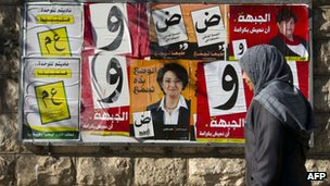 Woman walks past campaign poster for Israeli Arab candidates