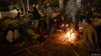 Supporters of Pakistani cleric Tahir-ul Qadri warm themselves around a fire