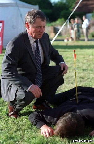 John Nettles examines corpse with arrow in back in Midsomer Murders
