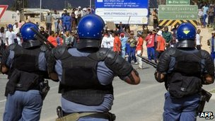 Police observer striking farm workers in South Africa's Western Cape province on 9 January 2013