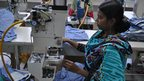 A woman operating a machine in a factory in Bangladesh