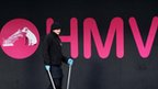 Man walks past HMV sign