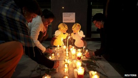 Women place candles outside the Public Ministry building to demand justice for the murdered girls