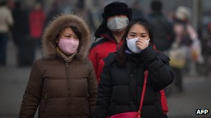 Women cover their noses and mouths while walking in Beijing