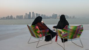 Women in Qatar sip coffee as they view the Doha skyline