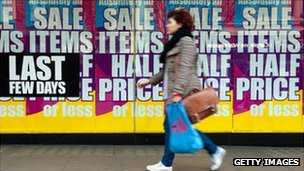 Woman walks past sales signs on Oxford Street in London