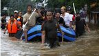Rescue workers evacuate residents from their flooded area in Jakarta on 17 January 2013