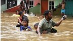 A father escorts his son as they evacuate a flooded area in Jakarta on 17 January 2013
