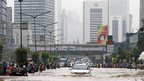 People wade through a flooded main road in Jakarta, Indonesia, on 17 January 2013