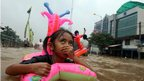 A girl uses an inflatable ring to wade through a flooded street in Jakarta, Indonesia, on 16 January 2013