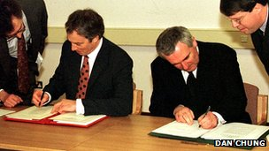 British Prime Minister Tony Blair (l) and Irish Taoiseach Bertie Ahern sign the Good Friday Agreement in Belfast on 10 April 1998