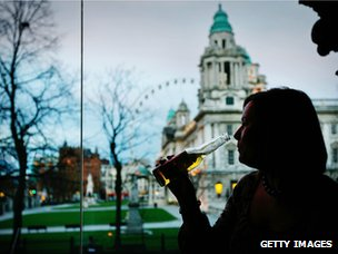 Woman drinking a beer in a bar in front of Belfast City Hall