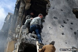 Libyan rebels help Hetherington out of damaged building in Misrata