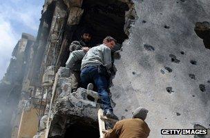 Libyan rebels help Hetherington out of damaged building in Misrata