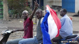 Malian people wave a French national flag