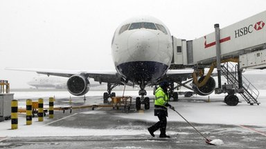 A British Airways worker clears snow on a stand at Terminal 5 of Heathrow Airport,